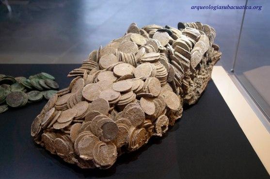 Conjunto de monedas extraidas del naufragio de la fragata Mercedes que conserva la forma de la caja que las contenía. ARQVA.